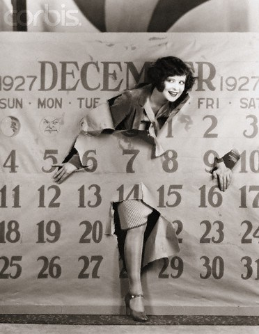 ca. 1920s --- Clara Bow (1905-1965), a famous American actress of the 1920s and 1930s, pokes through a giant calendar. --- Image by © Corbis